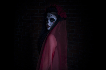 Woman in Halloween makeup - mexican Santa Muerte mask on dark background. Stock Photo