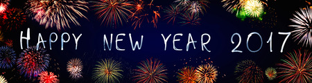 Happy new year 2017 written with neon light on black background with fireworks