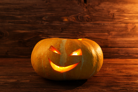 Jack o lanterns Halloween pumpkin face on wooden background Stock Photo