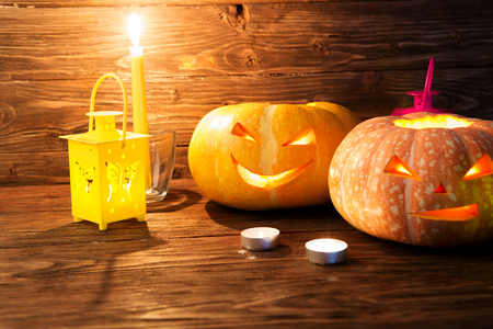 jack'o'lantern: Two pumpkin with candle over wooden background. Halloween pumpkin background. Jack-O-lantern. Stock Photo