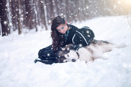 huskies: Fairy tale girl embracing cute dog in winter park. The girl with the husky or huskies. Dog dies Stock Photo
