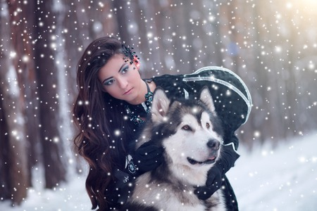huskies: Attractive woman with the dogs. Fairy tale girl with Huskies or Malamute. Christmas.