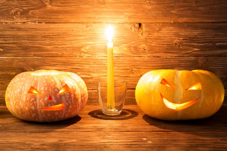 jack'o'lantern: Two pumpkin with candle over wooden background. Halloween pumpkin background. Halloween. Happy Halloween. jack-o-lantern. Halloween jack-o-lantern. Halloween pumpkins jack-o-lantern. Halloween pumpkin