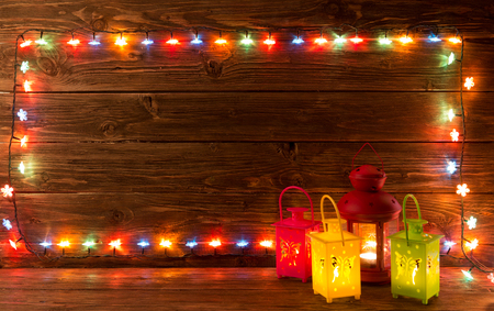 green lantern: Christmas garlands of lamps on a wooden background. Frame of Christmas lights and lantern. Merry Christmas.