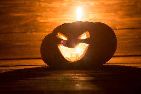 Jack o lanterns Halloween pumpkin face with candle on wooden background.