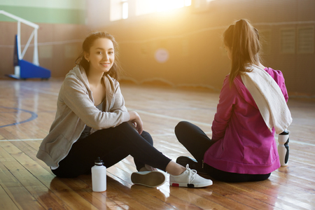 Two smiling women sitting on the wooden floor and relaxing after class in the gym Stock Photo