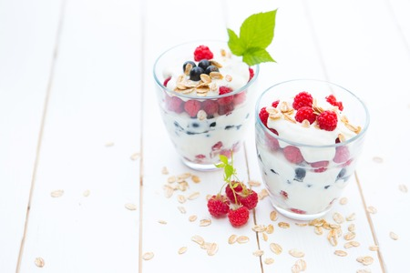 trifle: Healthy layered dessert with yogurt, granola, black currant and raspberries on wooden background Stock Photo