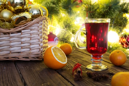 Mulled wine with ingredients on dark rustic vintage wooden table. Christmas hot red mulled wine in winter. Mulled wine with orange on christmas lights background.