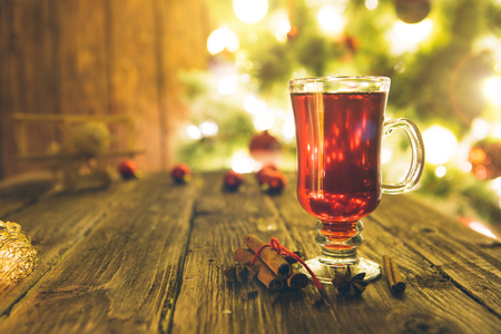 Christmas mulled wine in glass cup on a wooden table. Stock Photo