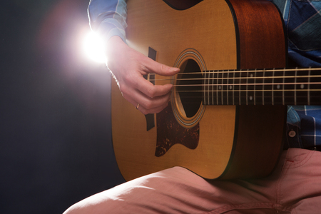 hand jamming: Man playing on acoustic guitar on dark background