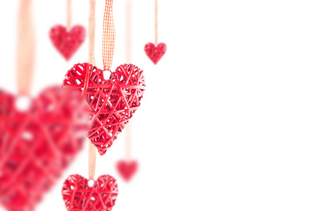 Few red hearts on the ribbon on a white background. Valentine's Day. Standard-Bild