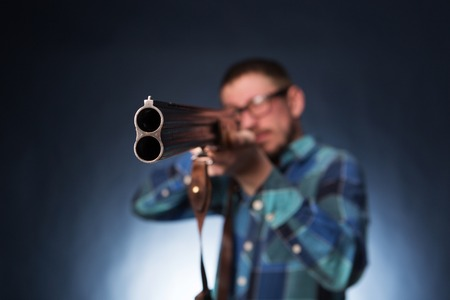 hysteria: Office worker holding a shotgun on dark blue background.