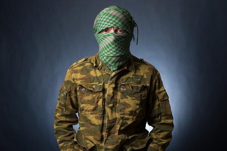 Terrorist in military uniform and mask on dark background
