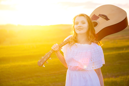 portrait of the beautiful young woman with guitar in the field Stock Photo