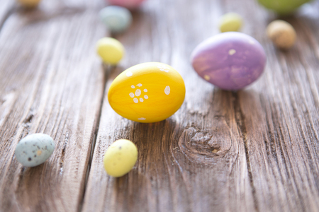 eastertime: Easter symbols on wooden background. Easter eggs on a rustic brown table. Stock Photo