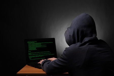 initiating: Hacker in hood with laptop initiating cyber attack. View from the back.