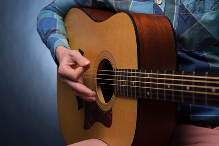hand jamming: Young man playing on acoustic guitar close up on dark blue background