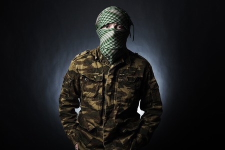 Terrorist in military uniform and mask on dark background