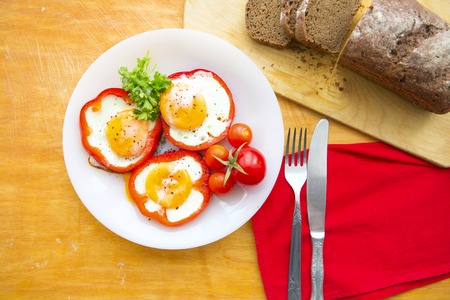 scrambled: Fried eggs in red peppers. Fried eggs in paprika served on white plate on wooden background Stock Photo