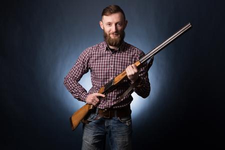 Man holding a shotgun on dark blue background.