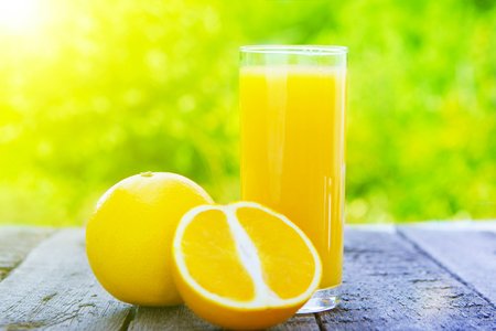 Glass of freshly squeezed orange juice standing on table on a summer day