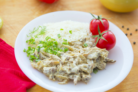 Beef Stroganoff with rice, tomatoes and greens on plate. Stock Photo