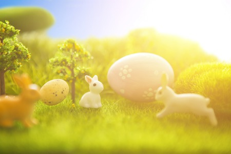 animal figurines: Rabbit and easter eggs in green grass with a blue sky. Macro.