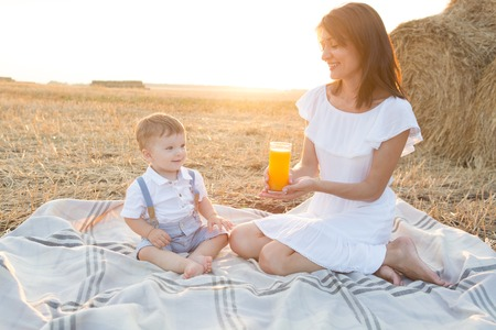 dressy: Mother and son outdoor in summer field. A family spending time together on picnic.