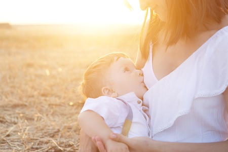Baby boy drinking breastmilk in nature over a sunset. Stock Photo - 75759919