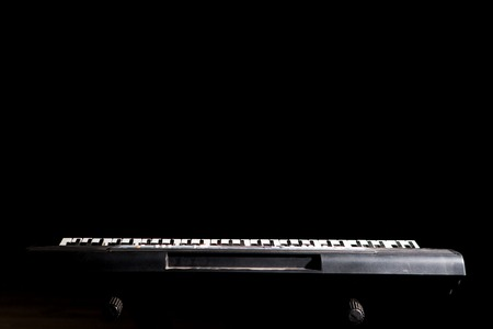 Synthesizer keyboard in the dark background with copy space.