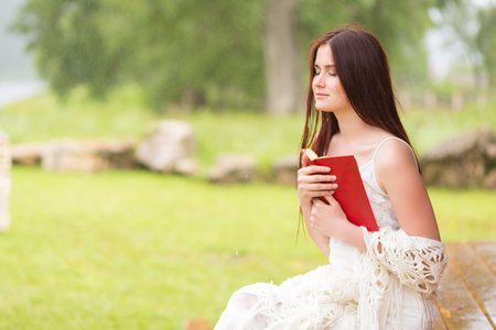 Pretty woman in white dress reading book in the cloudy nature. Girl sits on the terrace or on the porch.
