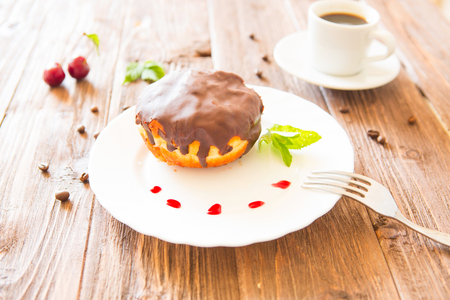 Chocolate donut or bun with an espresso on table. Stock Photo