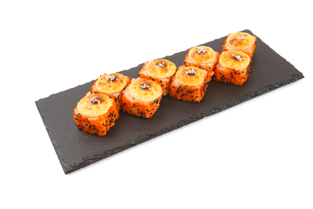 Japanese food. Baked sushi on a black slate surface, menu concept. Isolated on white.