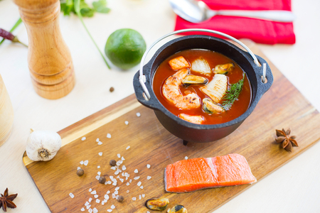 Restaurant cuisine, healthy delicatessen seafood soup on a cutting board.