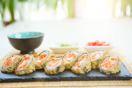 Hot sushi rolls served on black slate surface. Japanese food. Stock Photo
