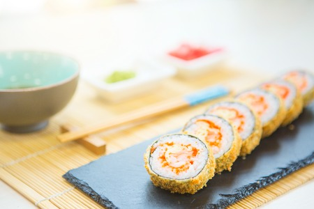 Hot fried Sushi Roll with cream cheese on black stone on bamboo mat decorated. Japanese cuisine.