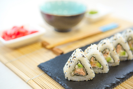 sake: Homemade sushi with salmon, omelet, cucumber and soft cheese. Rustic style.