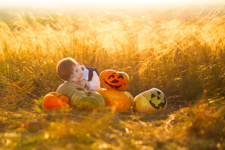 Cute boy enjoying autumn time. Little boy with pumpkins for Halloween over sunset or sunrise background.