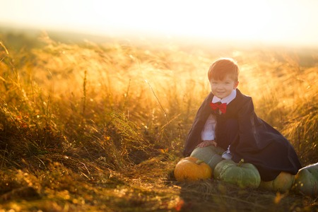 Happy young boy dressed as a dracula with pumpkins for Halloween. Stock Photo