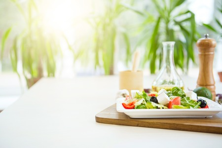 olive green: Fresh Greek salad on a plate on wooden cutting board.