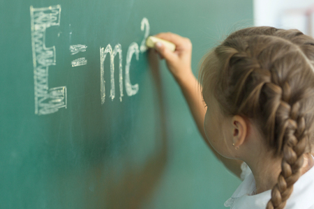Girl drawing on chalkboard formula e=mc2. Education and school concept.