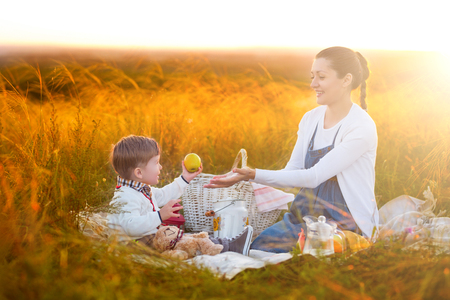 Mom feeds her son on a picnic. Mother and young son in sunny fall day. Happy family and healthy eating concept.