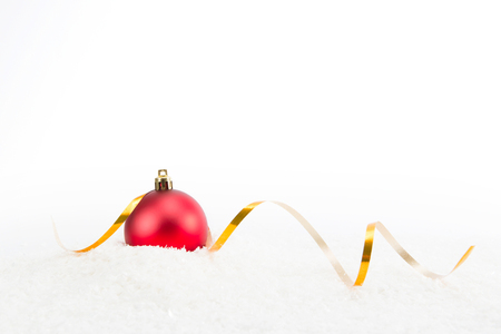 Red ball Christmas decoration with gold ribbon on snow isolated on white background. Space for your text.