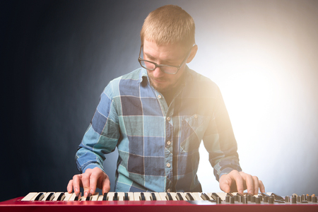 Musician playing keyboard on dark background. Musician concept. Stock Photo