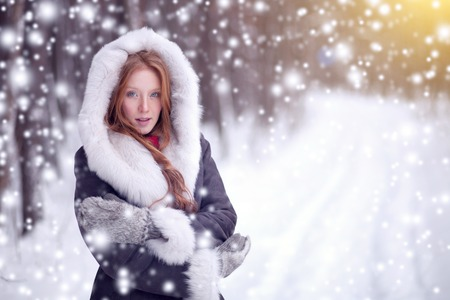 Beautiful girl in winter forest. Fairy tale. Snowfall. Christmas.