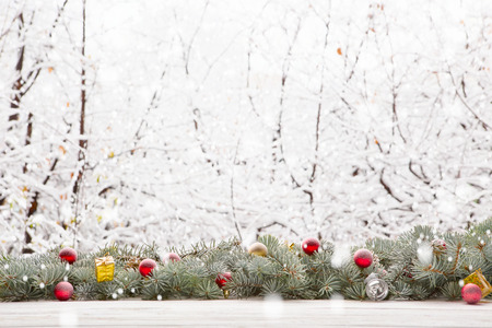 Christmas fir tree garland on wooden board on window sill over nature snowing tree park background with copy space.