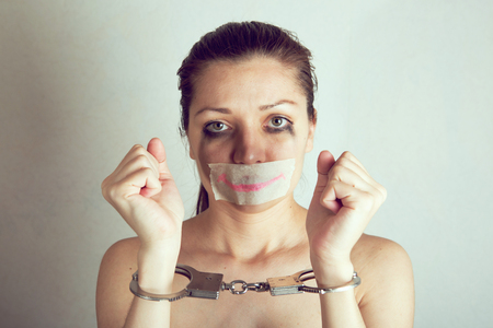 Unhappy woman with wrapped mouth by adhesive tape painted smile.
