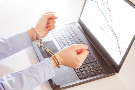 Woman hands in handcuffs with laptop with a financial graph on the screen. Stock Photo