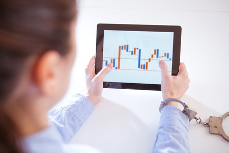 Hand attached with handcuffs and tablet with a financial graph on the screen. Stock Photo