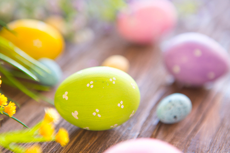 Easter eggs and spring flowers on rustic wooden background.